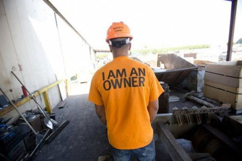 """Image of employee in hardhat with shirt that says """"I am an owner"""""""