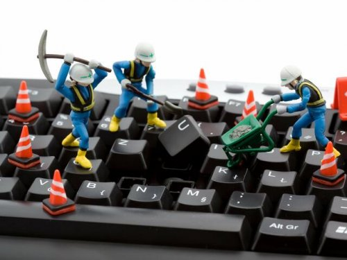 Toy construction workers are digging up keys on a keyboard