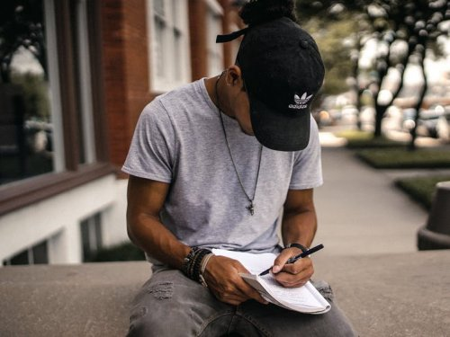Boy with a cap writting on a notebook