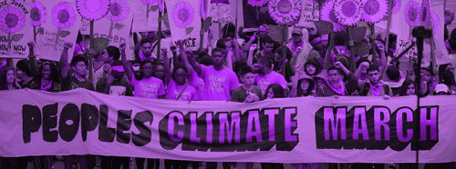 "Picture (through a purple filter) of people marching and holding a banner that says ""Peoples Climate March"""
