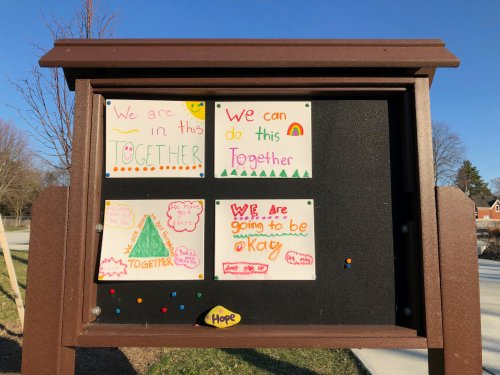 A neighbourhood bulletin board has 4 colourful, hand-drawn posters with positive messages. We are in this Together. We are going to be okay. Don't give up.