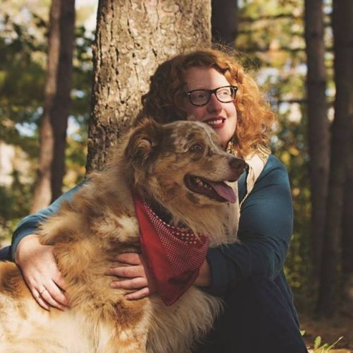 Katie Allen, smiling in the forest, hugging a dog.