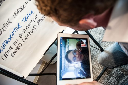 Image of people speaking via teleconference on a tablet while working on a whiteboard paper